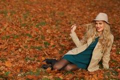 Młodej kobiety uśmiechnięty obsiadanie na trawie w jesieni spadku klonu ogródu żółty tło Piękna dziewczyna w żakiecie i opadający obrazy stock