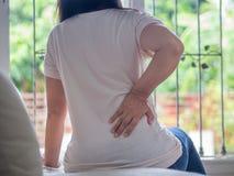 Młodej kobiety uczucia ból w jej z powrotem siedzieć na kanapie w domu zdjęcie royalty free