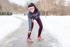 Młodej kobiety uczucia ból w nogach po jogging outside w zima parku obrazy royalty free