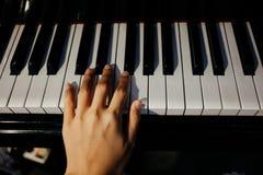 Młodej kobiety use lewej ręki sztuki pianino pianino klucz jest backgroun Zdjęcia Stock