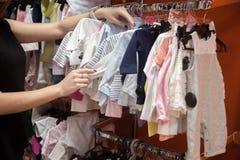 Młodej kobiety wybierać odziewa dla dziecka obraz stock
