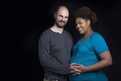 Młodej międzyrasowej pary matki pieszczotliwy brzuch Fotografia Royalty Free