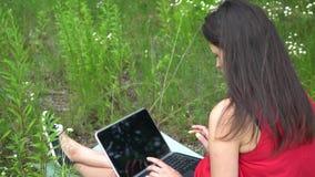 Młodej modnej kobiety pisać na maszynie klawiatura laptopa na zewnątrz z dziewczyna zbiory wideo