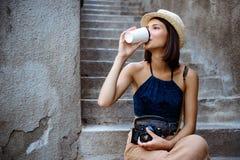 Młodej pięknej brunetki żeński fotograf pije kawę, siedzi przy schodkami Fotografia Stock