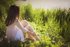 Młodej pięknej brunetki caucasian dziewczyna siedzi o w biel sukni Zdjęcie Stock