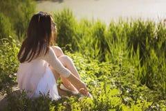 Młodej pięknej brunetki caucasian dziewczyna siedzi o w biel sukni Obrazy Stock