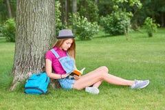 Młodej pięknej kobiety czytelnicza książka przy parkiem Obrazy Royalty Free