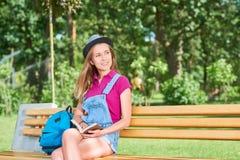 Młodej pięknej kobiety czytelnicza książka przy parkiem Obraz Stock