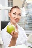 Młodej pięknej kobiety lekarki mienia uśmiechniętej zieleni świeży jabłko Zdjęcia Stock