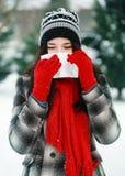 Młodej pięknej kobiety podmuchowy nos w zimie Fotografia Royalty Free