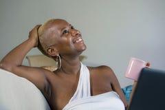 Młodej pięknej szczęśliwej czarnej afro Amerykańskiej kobiety uśmiechnięty działanie na laptopie w domu relaksował na kanapy leża Obrazy Stock