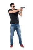 Młodej równiny odzieżowy policjant celuje armatni oddalonego z okularami przeciwsłonecznymi Boczny widok Fotografia Stock