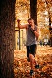Młodej seksownej atlety ćwiczy ciosy na drzewie w parku obraz stock