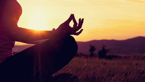 Młodej sportowej kobiety ćwiczy joga na łące przy zmierzchem Fotografia Stock