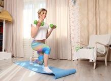 Młodej sporty atrakcyjnej kobiety sprawności fizycznej ćwiczy pojęcie, robi kucnięciom ćwiczy z dumbbells, pracujący out jest ubr Obrazy Royalty Free
