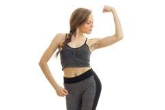 Młodej sprawności fizycznej dziewczyny popielaci sporty nadają się spojrzenia przy bicepsami na ręce obraz stock