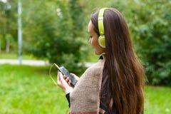 Młodej szczęśliwej kobiety słuchająca muzyka od smartphone z hełmofonami w zaciszność parku zdjęcie royalty free
