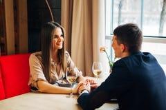 Młodej szczęśliwej pary napoju romantyczny daktylowy szkło biały wino przy restauracją, świętuje walentynki Fotografia Royalty Free