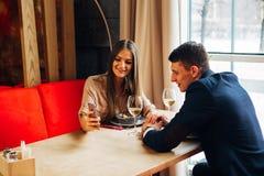 Młodej szczęśliwej pary napoju romantyczny daktylowy szkło biały wino przy restauracją, świętuje walentynki Zdjęcia Stock