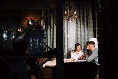 Młodej szczęśliwej pary napoju romantyczny daktylowy szkło czerwone wino przy restauracją, świętuje walentynki Zdjęcie Stock
