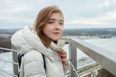 Młodej uroczej blondynki nastoletnia dziewczyna ma zabawę na obserwacja pokładzie z widokiem chmurnego wiosny nieba, marznąca rze Zdjęcie Stock
