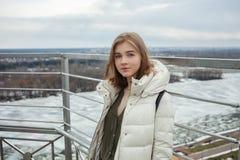 Młodej uroczej blondynki nastoletnia dziewczyna ma zabawę na obserwacja pokładzie z widokiem chmurnego wiosny nieba, marznąca rze Zdjęcie Royalty Free