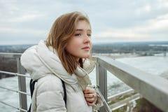 Młodej uroczej blondynki nastoletnia dziewczyna ma zabawę na obserwacja pokładzie z widokiem chmurnego wiosny nieba, marznąca rze Obraz Royalty Free