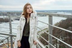 Młodej uroczej blondynki nastoletnia dziewczyna ma zabawę na obserwacja pokładzie z widokiem chmurnego wiosny nieba, marznąca rze Obrazy Stock