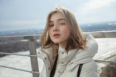 Młodej uroczej blondynki nastoletnia dziewczyna ma zabawę na obserwacja pokładzie z widokiem chmurnego wiosny nieba, marznąca rze Zdjęcia Royalty Free