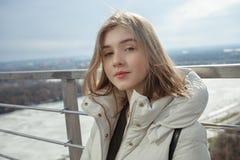 Młodej uroczej blondynki nastoletnia dziewczyna ma zabawę na obserwacja pokładzie z widokiem chmurnego wiosny nieba, marznąca rze Zdjęcia Stock