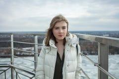Młodej uroczej blondynki nastoletnia dziewczyna ma zabawę na obserwacja pokładzie z widokiem chmurnego wiosny nieba, marznąca rze Fotografia Royalty Free
