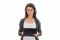 Młodej uroczej brunetki biznesowa kobieta z hełmofonami i mikrofon robimy notatkom odizolowywać na białym tle Obraz Royalty Free