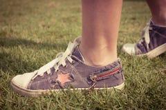 Młodość sneakers na dziewczyn nogach na trawie Obrazy Stock