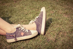 Młodość sneakers na dziewczyn nogach na trawie Fotografia Stock