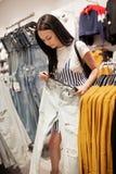 Młodociana ładna dama z długie włosy, będący ubranym przypadkowych ubrania, wybiera nowych cajgi w sławnym sklepie fotografia stock
