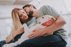 Młodociana całowanie para obejmuje ich wśliznie psa fotografia stock