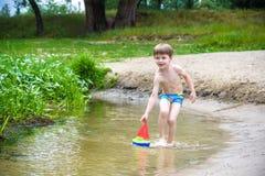młodszy brat bawić się z papierowymi łodziami rzeką na ciepłym i pogodnym letnim dniu Obraz Stock