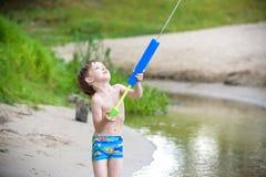 młodszy brat bawić się z papierowymi łodziami rzeką na ciepłym i pogodnym letnim dniu Zdjęcia Royalty Free