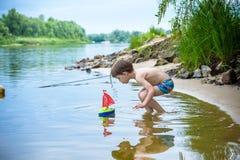 młodszy brat bawić się z papierowymi łodziami rzeką na ciepłym i pogodnym letnim dniu Fotografia Stock