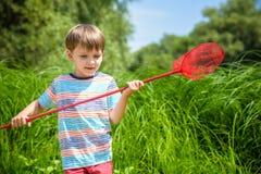 młodszy brat bawić się z papierowymi łodziami rzeką na ciepłym i pogodnym letnim dniu Zdjęcia Stock