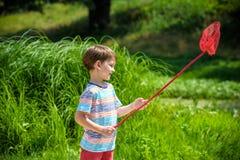 młodszy brat bawić się z papierowymi łodziami rzeką na ciepłym i pogodnym letnim dniu Zdjęcie Stock