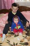 Młodszy brat i siostra siedzimy na łóżku w pokoju Zdjęcie Stock
