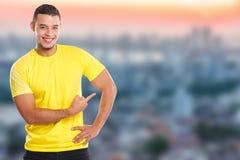 Młody łaciński mężczyzna pokazuje wskazujący marketingowych grodzkich reklamy ogłoszenia ludzi copyspace kopii przestrzeń obrazy royalty free