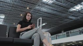 Młody Ładny bizneswoman Używa Smartphone przy lotniskiem Podczas gdy Czekający Jej kolejkę Dla rejestraci, Podróżny pojęcie Zdjęcia Royalty Free