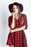 Młody ładny brunetki dziewczyny modniś up marzy uśmiecha się w kapeluszu na białego tła przypadkowym zakończeniu istna amerykańsk Zdjęcia Stock