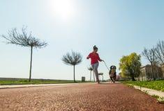 Młody ładny dziewczyny biegać plenerowy z jej Bernese góry psem Obrazy Royalty Free