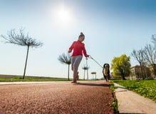 Młody ładny dziewczyny biegać plenerowy z jej Bernese góry psem Obrazy Stock