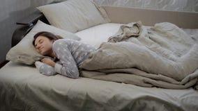 Młody ładny dziewczyny dosypianie pod koc na łóżku Przy niektóre punktem decyduje obracać na jego stronie i ziewał zbiory