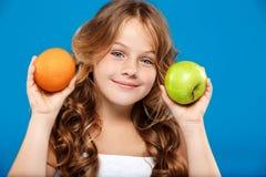 Młody ładny dziewczyny mienia jabłko i pomarańcze nad błękitnym tłem Obraz Stock