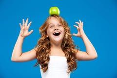 Młody ładny dziewczyny mienia jabłko na głowie nad błękitnym tłem Zdjęcie Stock
